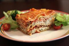Slice of lasagne with green salad and red cherry tomatoes